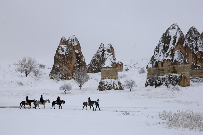 Beyaza bürünen Kapadokyada peri bacaları arasında atlı safari
